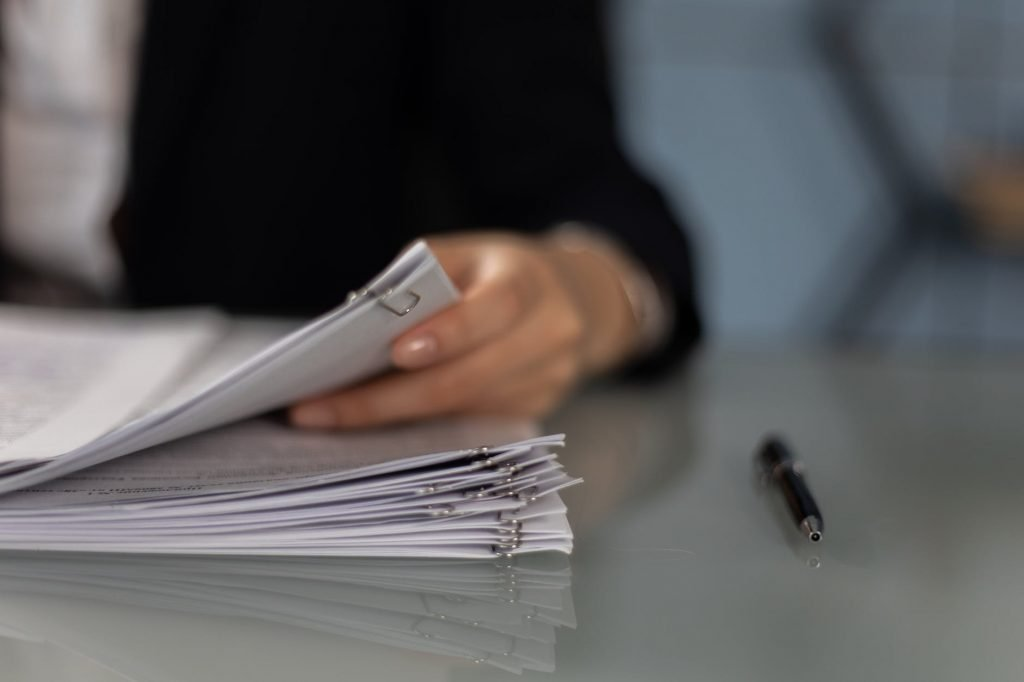 close up shot of a person holding a paperwork beside a pen
